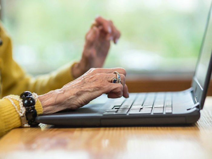 The hands of an older woman tapping laptop keys
