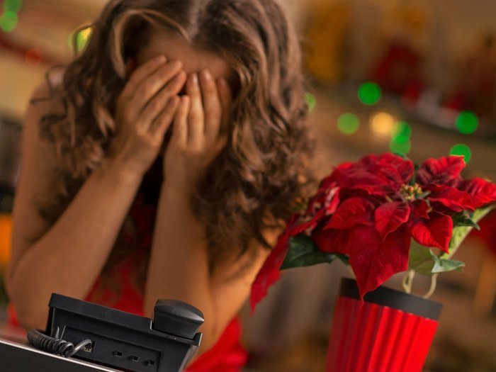 A woman takes in sad news, in a room decorated for Christmas