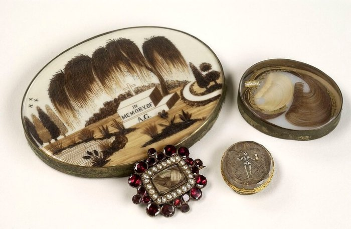 Pieces of Victorian morning jewellery: two brooches and a trinket box decorated with human hair and red gemstones. One of the brooches has a tiny figure of a skeleton.