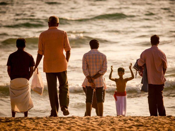 A Hindu family prepares to bathe in the sea before performing rituals for Pitru Paksha