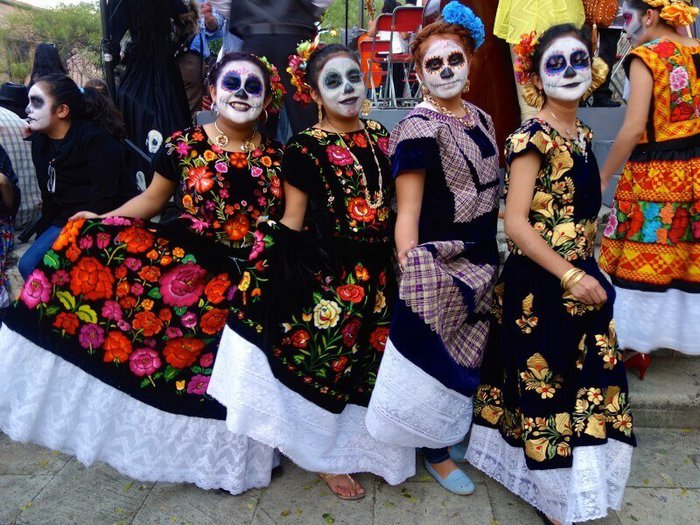 Three Mexican woman celebrating Day of the Dead, in traditional costume and skull face paint