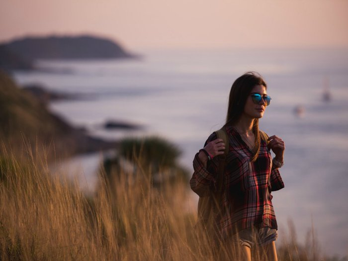 A backpacker walking on a clifftop overlooking a beautiful ocean at sunset