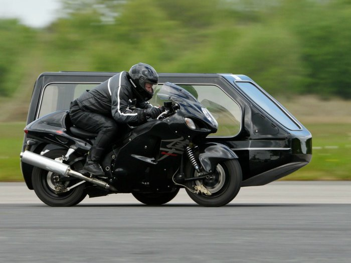 A photo of a motorcycle hearse going at speed