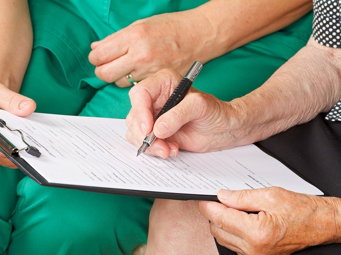 Woman signing a medical form