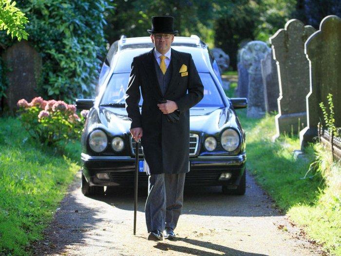 Funeral director Scott Watters leading a funeral cortege