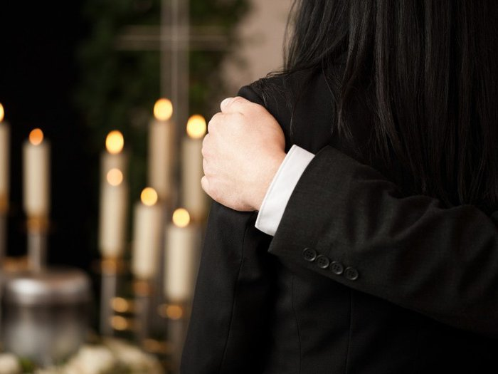 Rear view of man and woman in black funeral clothes, with man's arm around the woman