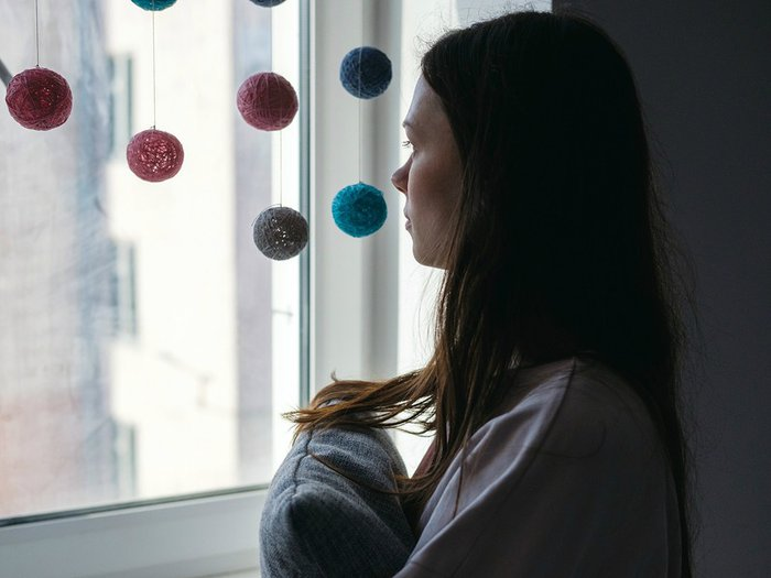 A young woman hugging a cushion gazes out of a window