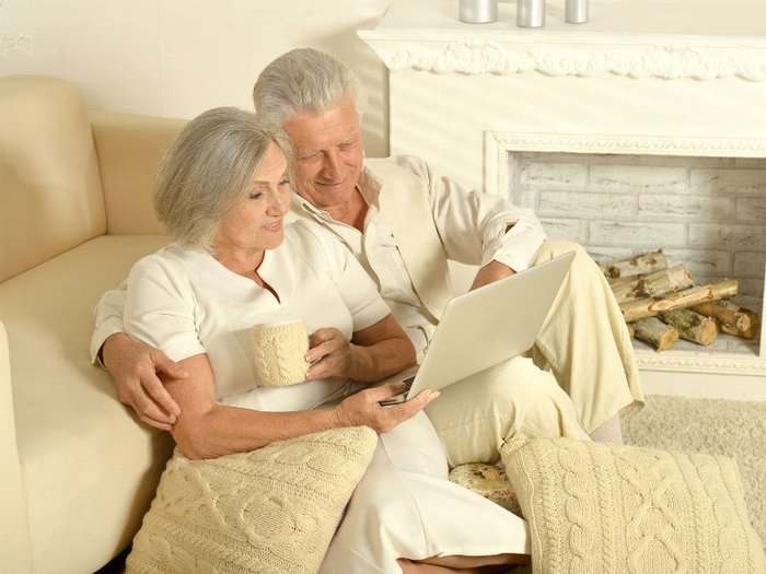 A couple sitting down at home choosing a funeral plan online