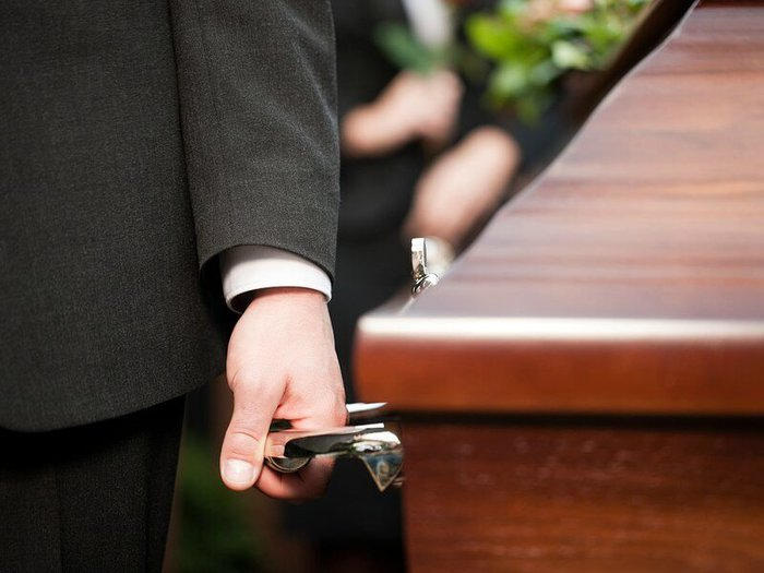 Pallbearers carrying a casket out of a church