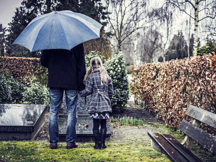 Grieving widower and daughter standing at a grave