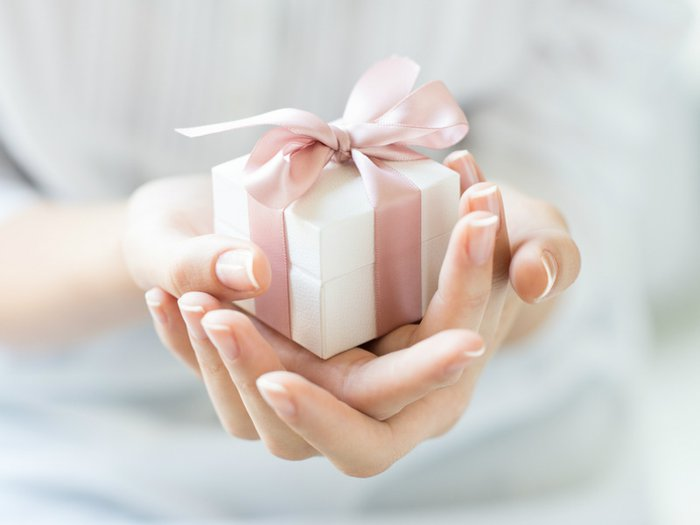 Woman holding out a sympathy gifts for a bereaved friend