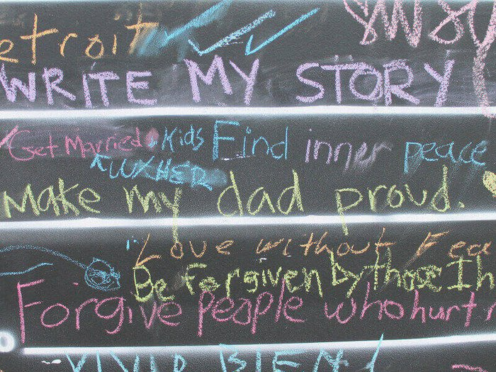 Close-up of Before I Die chalkboard, created by Candy Chang. People have written their aspirations in chalk.