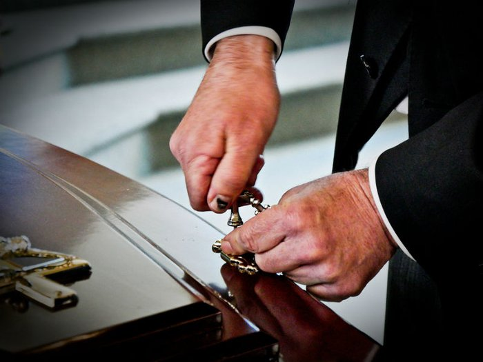 The CMA has proposed an investigation into the UK's funeral industry. Picture shows a funeral director closing a coffin