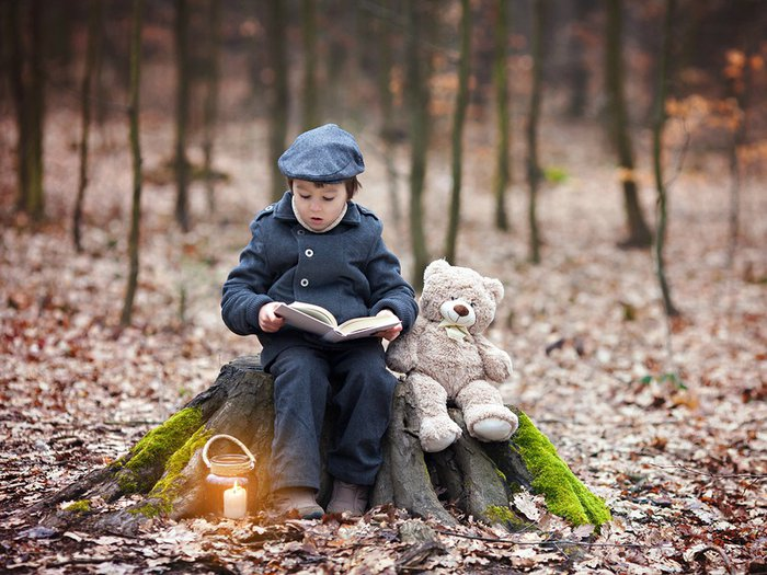 A child reading a book next to his teddie bear