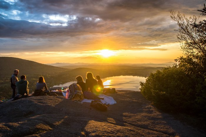 A group of people sitting on rocks on top of a hill at sunset with a picnic