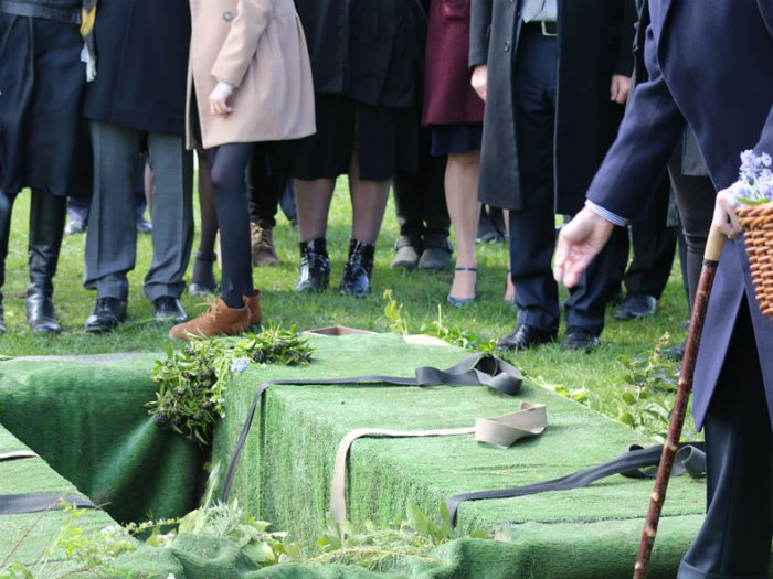Mourners scatter soil and flowers in a grave