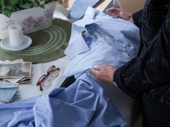 A bereaved woman sorting through her late husband's belongings
