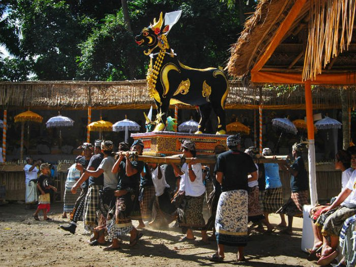 A decorative ox-shaped coffin is carried by mourners
