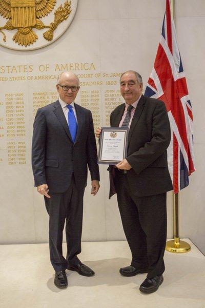 Tony collcting his award from the Ambassador