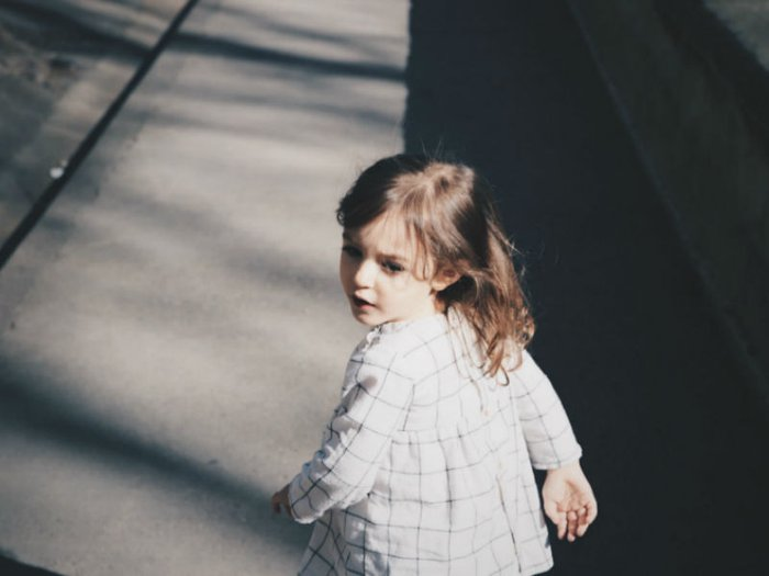 A small child walking along a dark path