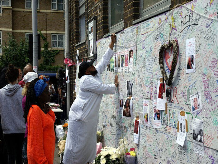 A man writing on a tribute wall for the Grenfell Tower victims