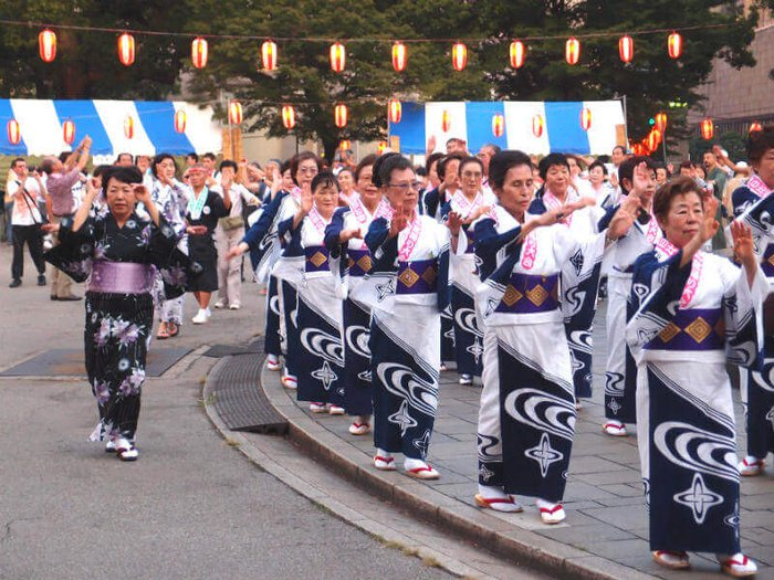 Women dressed in kimonos performing Bon Odori to celebrate Obon.