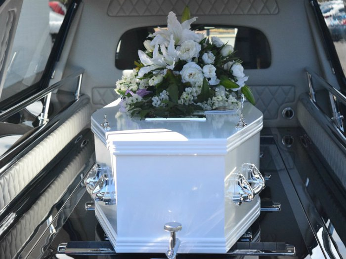 Coffin with floral presentation in hearse