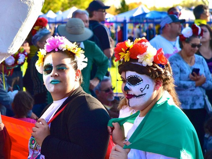 Two woman with skull facepaint and flowers in their hair at a Day of the Dead festival in Albequerque, New Mexico