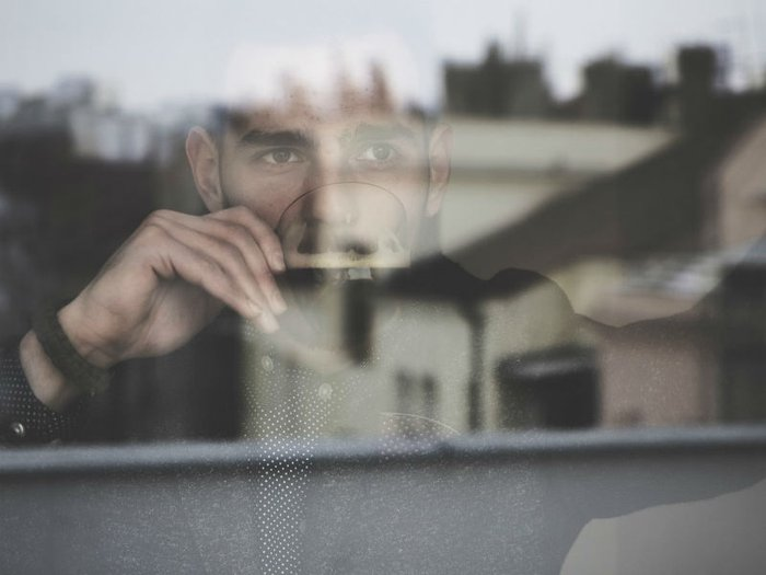 A bereaved man lost in thought gazes out of a window