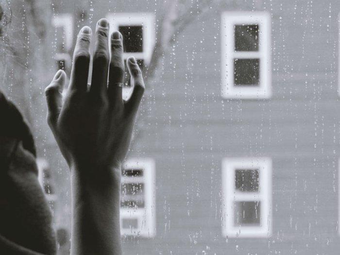 grief intervention: hand on rainy window