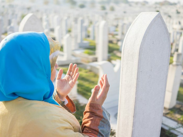 Muslim woman praying at an Islamic cemetery