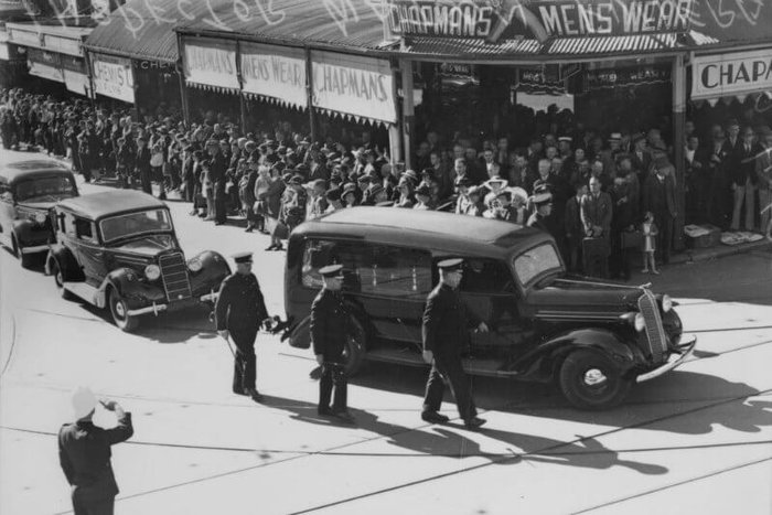 A motor car leads a funeral procession, watched by hundreds