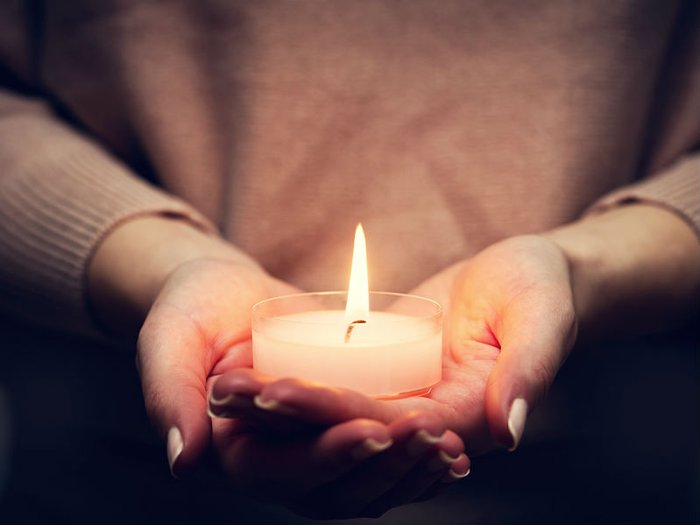 A woman holds a lit tealight in her cupped hands