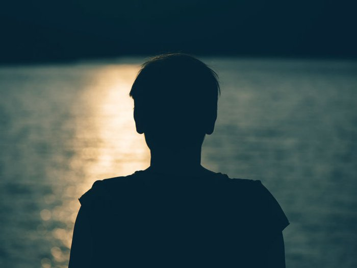 delayed grief: Silhouette of a person in darkness