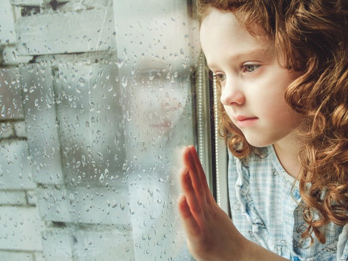 A bereaved young girl looking out of a window