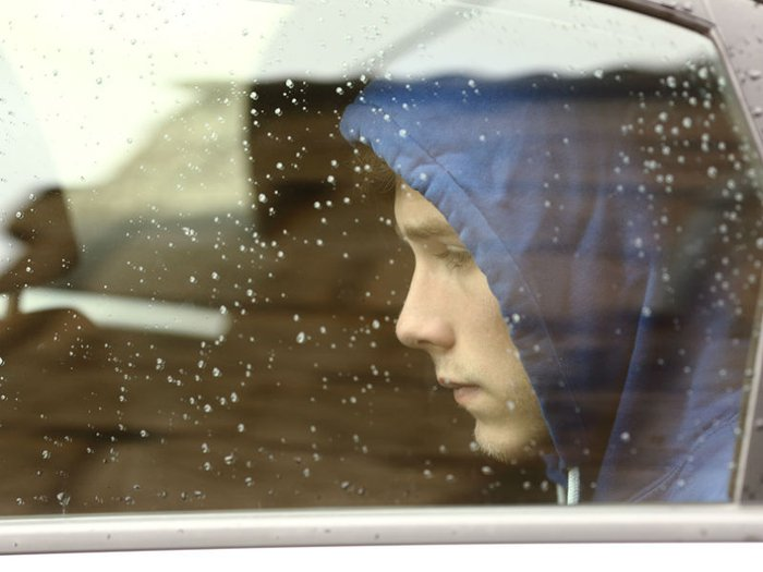 Bereaved young man sitting in car, looking out of the window