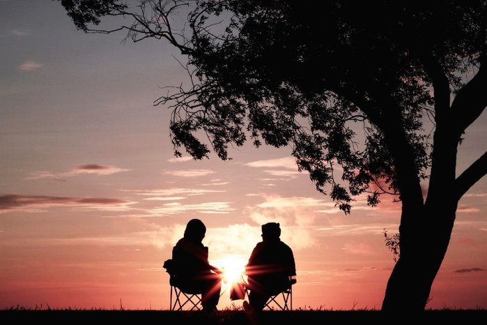 Two people in silhouette sitting in camp chairs with pink sunset in the distance