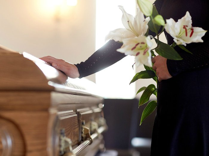 A mourner pays their respects at a funeral