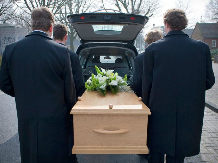 Pallbearers carrying a coffin to the hearse for a funeral service