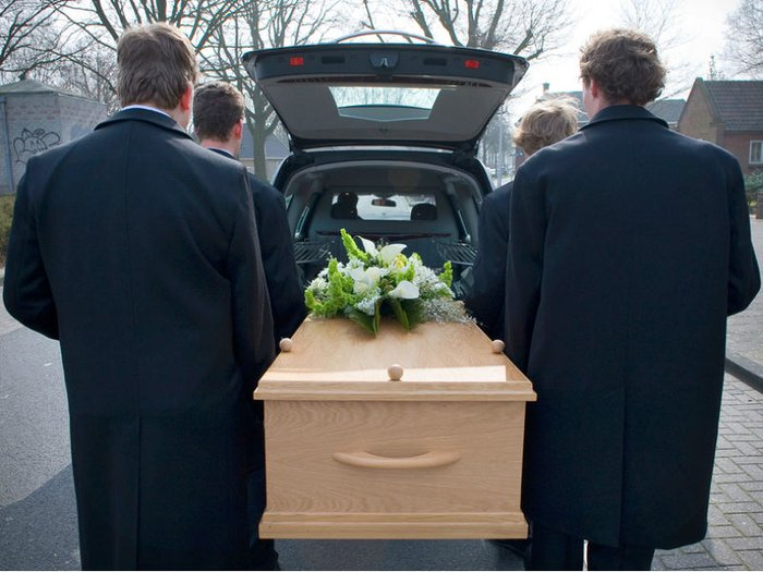 A coffin is carried to a hearse