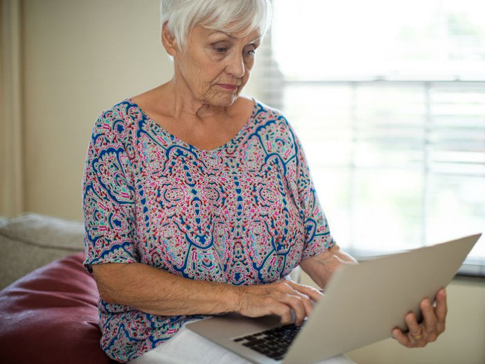 A pensive-looking woman looking at her laptop