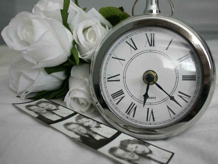 Old photographs, a clock and flowers hint at memories of a much-missed loved one