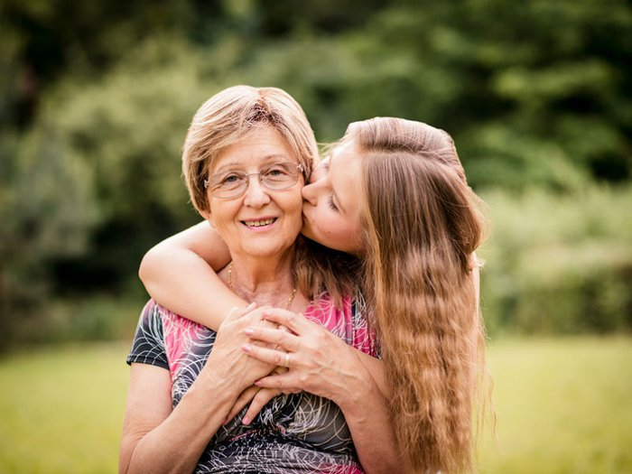 A granddaughter kisses her smiling grandmother on the cheek