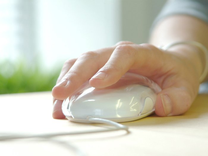 Person using a computer mouse, accessing online services for the bereaved