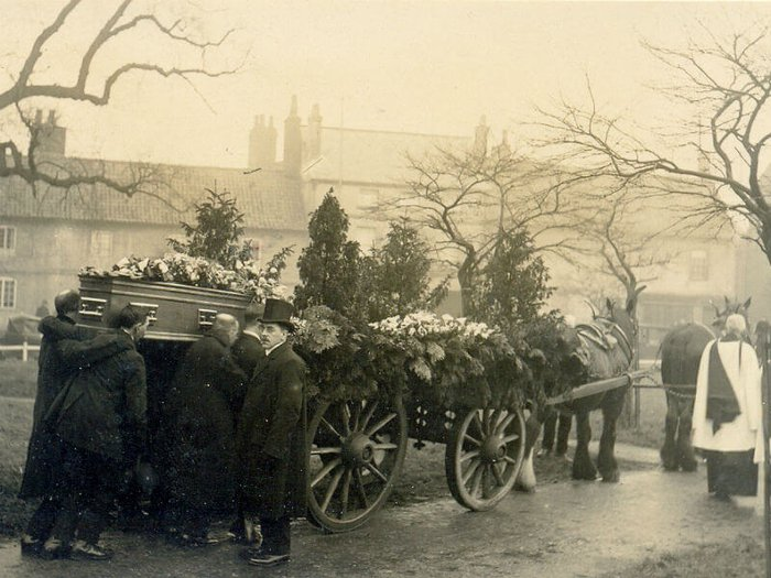 Horse drawn hearse with pallbearers and funeral directors