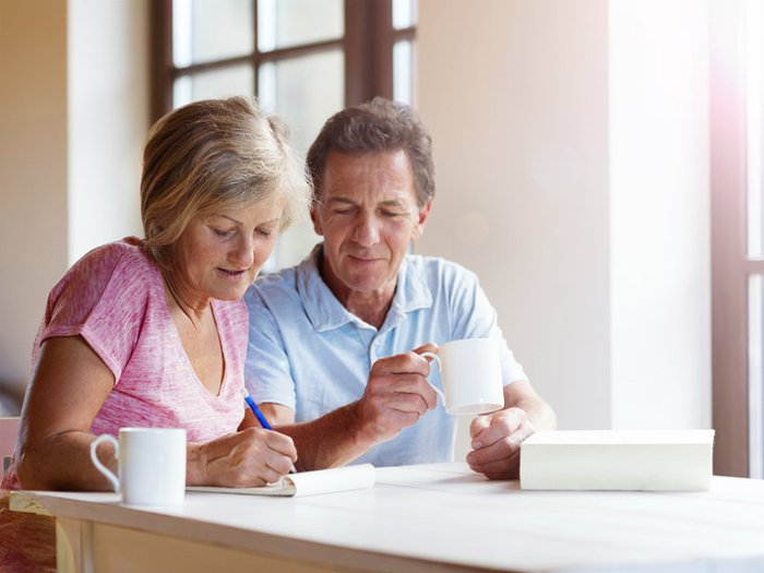 Middle-aged couple making plans for the end of life, reading paperwork at the table