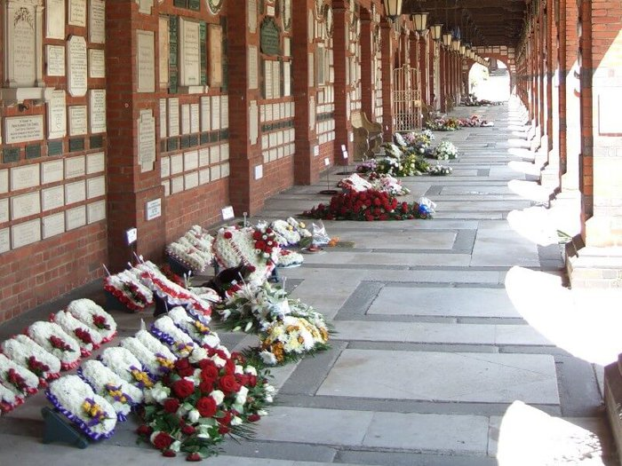 Floral displays in cloister outside Golders Green Crematorium, with memorial plaques on the wall