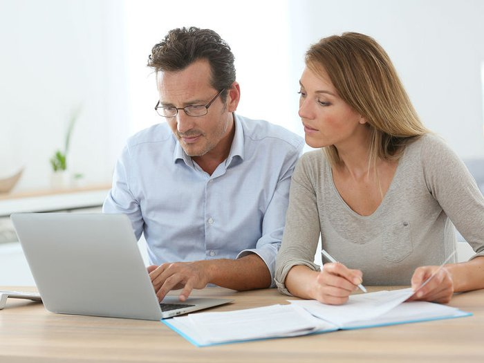 Middle-aged couple making plans for later life, reading paperwork at the table