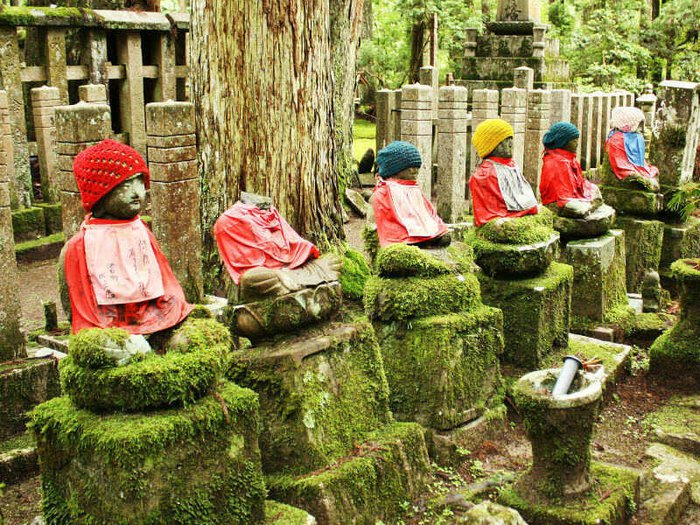 Jizo statues in a row at Okunoin Cemetery, dressed in woollen hats and red bibs
