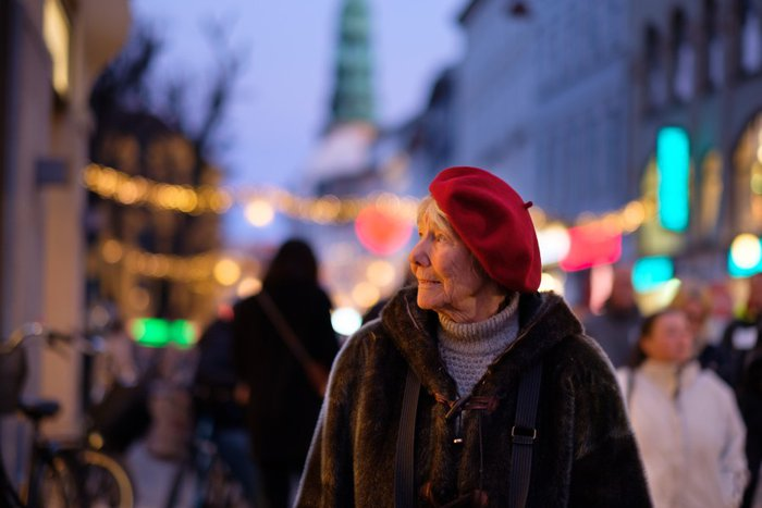 Older woman in red beret on a high street looking to her left